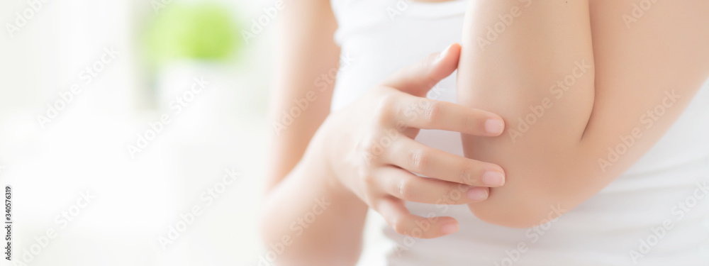 Fototapeta Closeup elbow of beautiful asian woman applying skincare and moisturizer cream or treatment for scratch and itchy, asia girl applying cream and lotion skin care with cosmetic makeup, banner website.