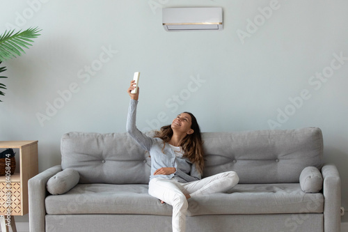 Smiling young woman relaxing on couch in living room, using air conditioner remote controller, switching, beautiful girl setting comfort temperature at home, enjoying fresh air, resting on sofa