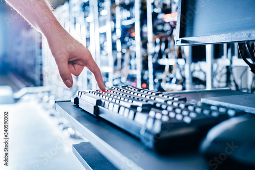 Leinwand Poster IT specialist pressing red button on keyboard in big data center.