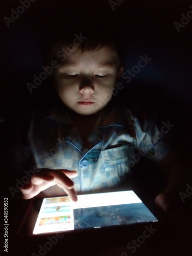 Obraz Close-up Of Boy Using Digital Tablet While Sitting In Darkroom - fototapety do salonu