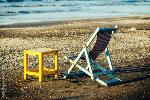 Canvas Empty Deck Chair By Table On Shore At Beach