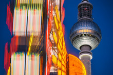 Low Angle View Of Spinning Ferris Wheel By Fernsehturm Tower Against Sky