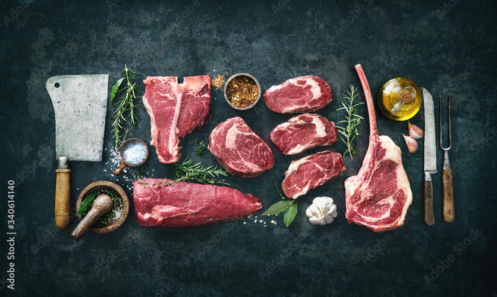Fototapeta Variety of raw beef meat steaks for grilling with seasoning and utensils - obraz na płótnie
