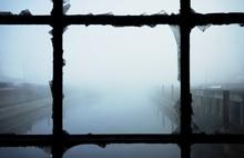 Calm Lake During Foggy Weather Seen Through Broken Window