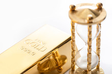 Hourglass And Fine Gold Bullion On White Background.