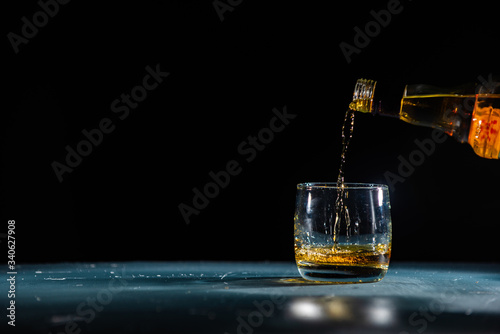 Carta da parati whiskey pouring from a bottle into a glass on a black background with bright hig