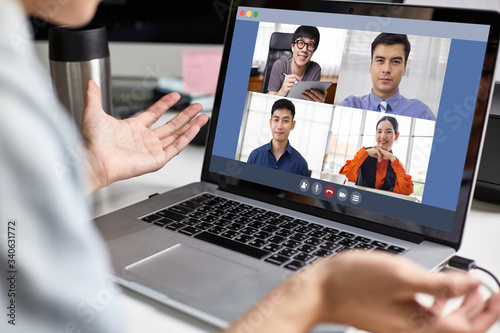 Fototapeta Back view of Asian business man or creative using laptop video conference talking with corporate team, meeting online, work from home and working remotely, group of people discuss about project report obraz na płótnie