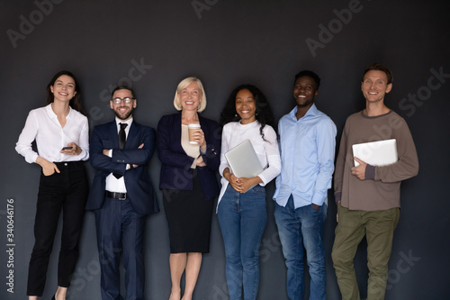 Fotografie, Obraz Group picture of smiling multiethnic diverse businesspeople stand posing near bl