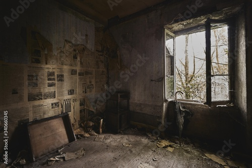 Photo Old room with the walls covered in newspapers under the lights in an abandoned b