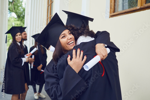 Photo Graduates with diplomas in their hands hugging
