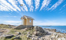An Ancient, Yellow Wooden House With A Flag Pole And The Swedish Flag Near The Sea In Torekov, Sweden