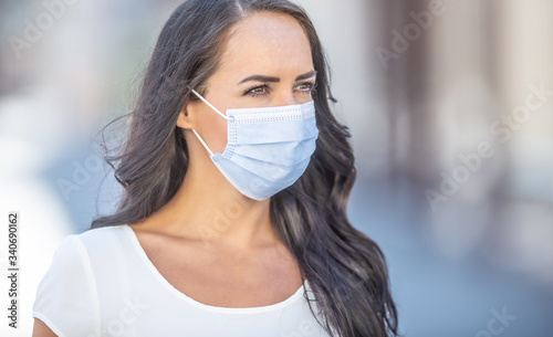 Fotografija Disposable face mask on a face of young dark-haired female looking to the side