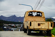 Run Down Or Decomissioned Pick Up Truck Parked On Street On Hill In Ushuaia, Patagonia In Argentina With Mountain Range And Houses In Background
