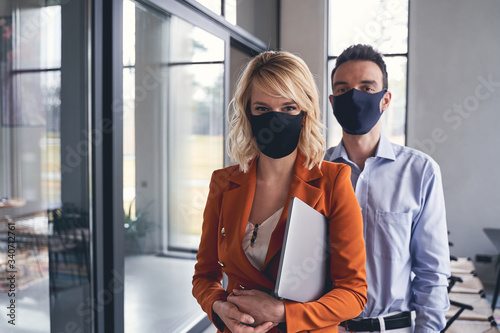 Smiling businesswoman and her serious colleague standing indoors