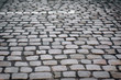 The gray paving stones close up. The texture of the old dark stone. Vintage, grunge. Road surface.