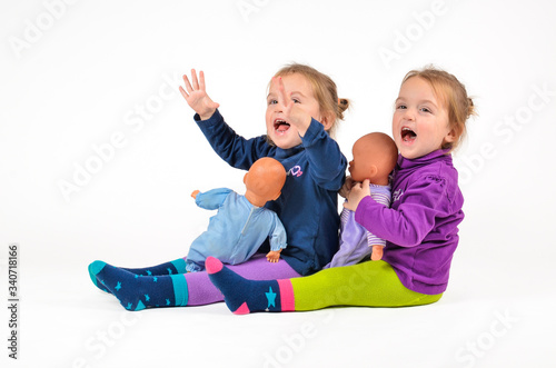 Fototapeta Happy Twin Baby Girls Playing With Dolls Against White Background