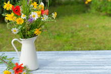 Wild Flower Bouquet In White Jug On Blue Vintage Wooden Table. Still Life With Bouquet Of Spring Wildflowers Against Green Natural Backdrop. Summer Day. Beautiful Floral Background. Copy Space.