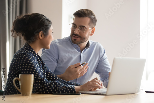 Different ethnicity millennial co-workers indian woman and caucasian man sit at desk discuss new project or task, share information brainstorm creative innovative ideas, teamwork and thinking concept