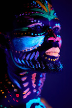 Mysterious African Male With Fluorescent Body Art Glowing In Dark Space. Fashion Model Posing At Camera, He Feels The Rebirth Of The Soul