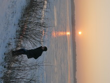 Person On Snow Covered Field By Frozen Lake Against Sky During Sunset