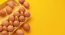 Brown Chicken Eggs In Cardboard Box On Yellow Background, Top View