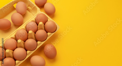 Brown chicken eggs in cardboard box on yellow background, top view Wallpaper Mural