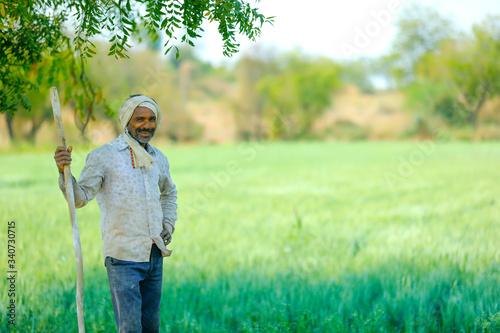 Young Indian farmer standing at wheat field Slika na platnu