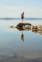 Man Walking On Rocky Lake Shore