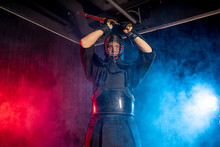 Caucasian Male Kendo Fighter In Traditional Japanese Style Of Clothing, Protective Armour, Using Shinai. Practicing Fight Isolated Over Smoky Room