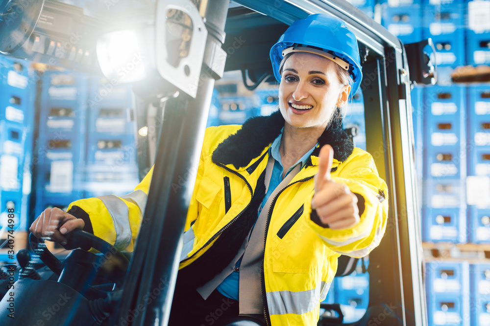 Fototapeta Worker woman showing thumbs up in logistics delivery center
