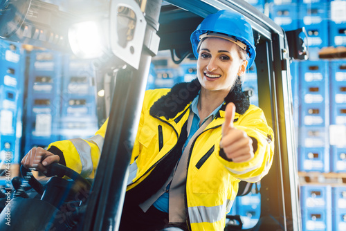 Obraz na płótnie Worker woman showing thumbs up in logistics delivery center