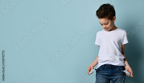 Small cute boy with modern hairstyle in white t-shirt standing and showing empty Фотошпалери