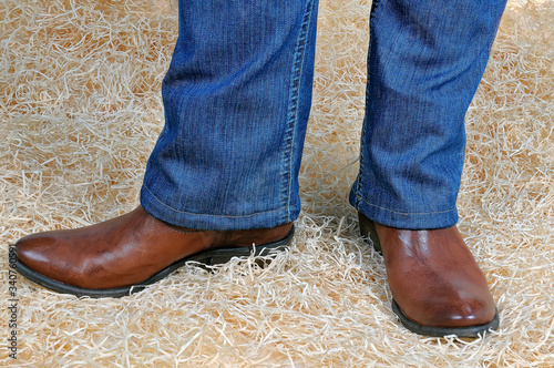 Pair of legs in traditional vintage brown cowboy boots and blue classic jeans po Canvas-taulu
