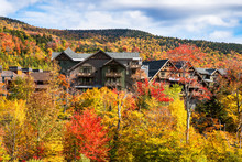 Holiday Apartment Buildings Among Colourful Trees In A Mountain Landscape On Acloudy Autumn Day