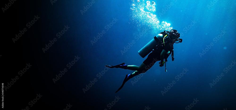Fototapeta Woman scuba diving in deep blue sea banner on black background