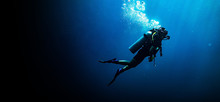 Woman Scuba Diving In Deep Blu...