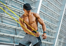 Athletic Man Performs Exercises Using Resistance Band. Photo Of Strong Man Training In The City. Strength And Motivation