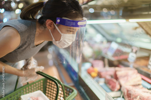 Fotografía Woman wearing gloves, face shield and mask choosing meat at supermarket