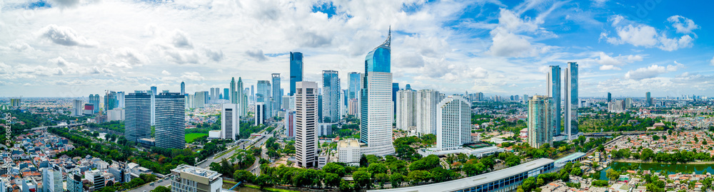 Fototapeta Aerial View of Jakarta Downtown Skyline with High-Rise Buildings With White Clouds and Blue Sky, Indonesia, Asia