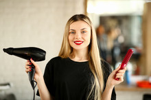 Young Hairstylist Holding Blow Dryer And Hairbrush. Blonde Hairdresser Showing Hairdryer And Red Comb For Haircut Styling. Stylist Using Professional Equipment For Making Hairdo Looking At Camera Shot