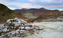 Pile Of Stones Marking The Way In A Frost Covered Valley Below The Summit Of Cat Bells, Derwent Fells With The Mountain Summit Of Causey Pike In The Distance. Lake District UK.