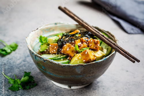 Fotografia Vegan tofu poke bowl with rice, cucumber, avocado and nori, gray background