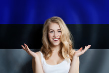 Beautiful Happy Young Woman Against The Estonian Flag Background. Live, Education And Work In Estonia