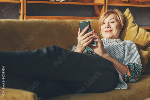 Senior lady with smart phone resting at home Canvas Print