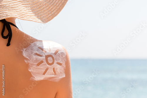 Foto Sunscreen lotion in sun shape on tanned woman's shoulder
