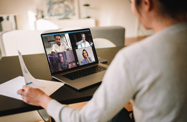 Businesswoman at home having a video conference with her team