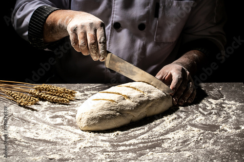Fotografia, Obraz Baker making patterns on raw bread using a knife to shape the dough prior to baking
