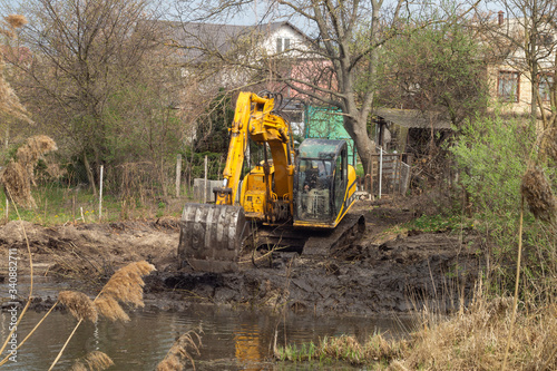 Fényképezés Crawler excavator or digger dredges on the lake