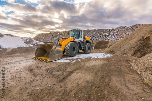 Fotografie, Obraz Excavator in a quarry extracting and moving stone for its transformation