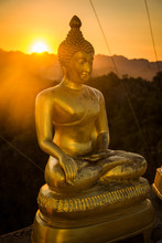 Golden Buddha Statue In Thailand At Sunset With Mountains Landscape In The Background